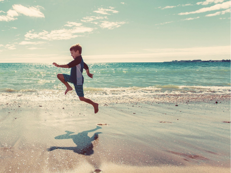 boy jumping along the sand on the beach