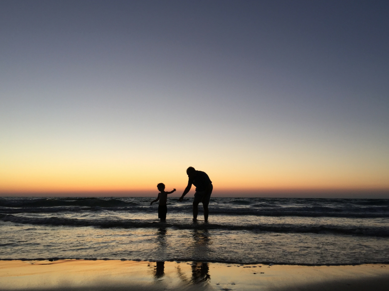 grandfather and son in the sea on the beach